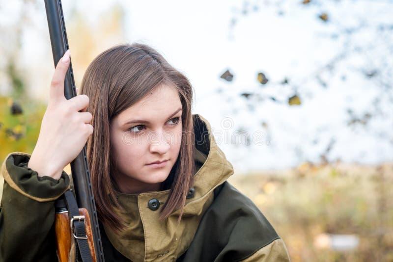 Portret van een mooi jong meisje in camouflagejager met jachtgeweer royalty-vrije stock fotografie
