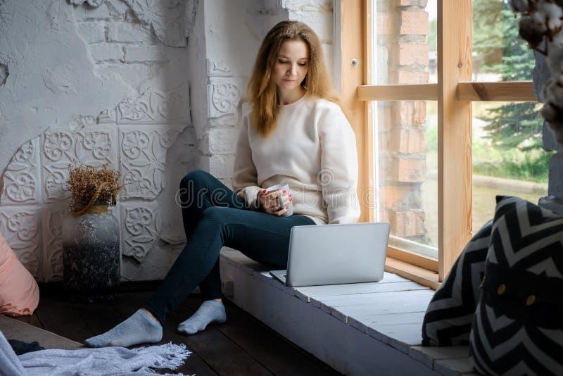 Portret van een mooi jong meisje dat in de ochtend op de vensterbank met een laptop boek zit en koffie drinkt stock fotografie