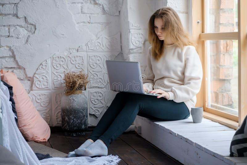 Portret van een mooi jong meisje dat in de ochtend op de vensterbank met een laptop boek zit en koffie drinkt stock foto