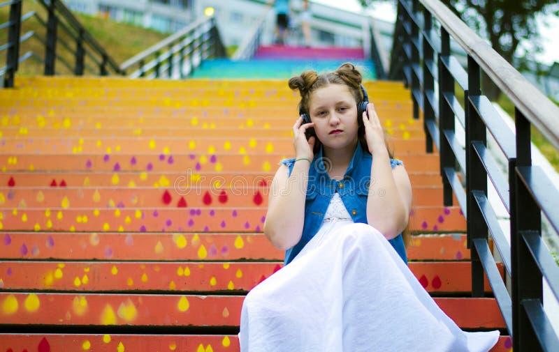 Portret van een mooi, jong meisje dat op de treden zit en aan muziek op hoofdtelefoons, in de straat, in de zomer luistert royalty-vrije stock fotografie