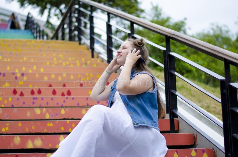 Portret van een mooi, jong meisje dat op de treden zit en aan muziek op hoofdtelefoons, in de straat, in de zomer luistert stock foto