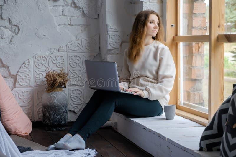 Portret van een mooi jong meisje dat op een vensterbank in de ochtend met een laptop boek op haar knieën zit en uit kijkt royalty-vrije stock foto