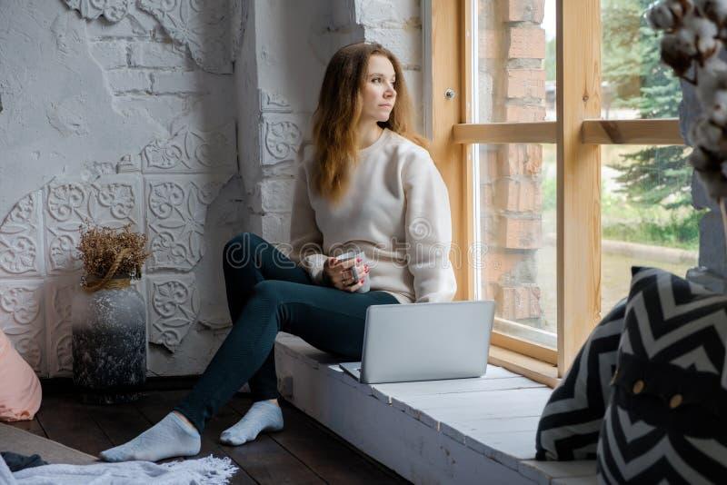 Portret van een mooi jong meisje dat op een vensterbank in de ochtend met een laptop boek op haar knieën zit en uit kijkt stock afbeelding
