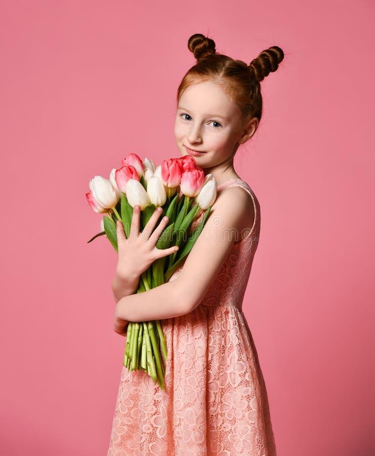 Portret van een mooi jong meisje die in kleding groot die boeket van irissen en tulpen houden over roze achtergrond worden geïsol stock fotografie