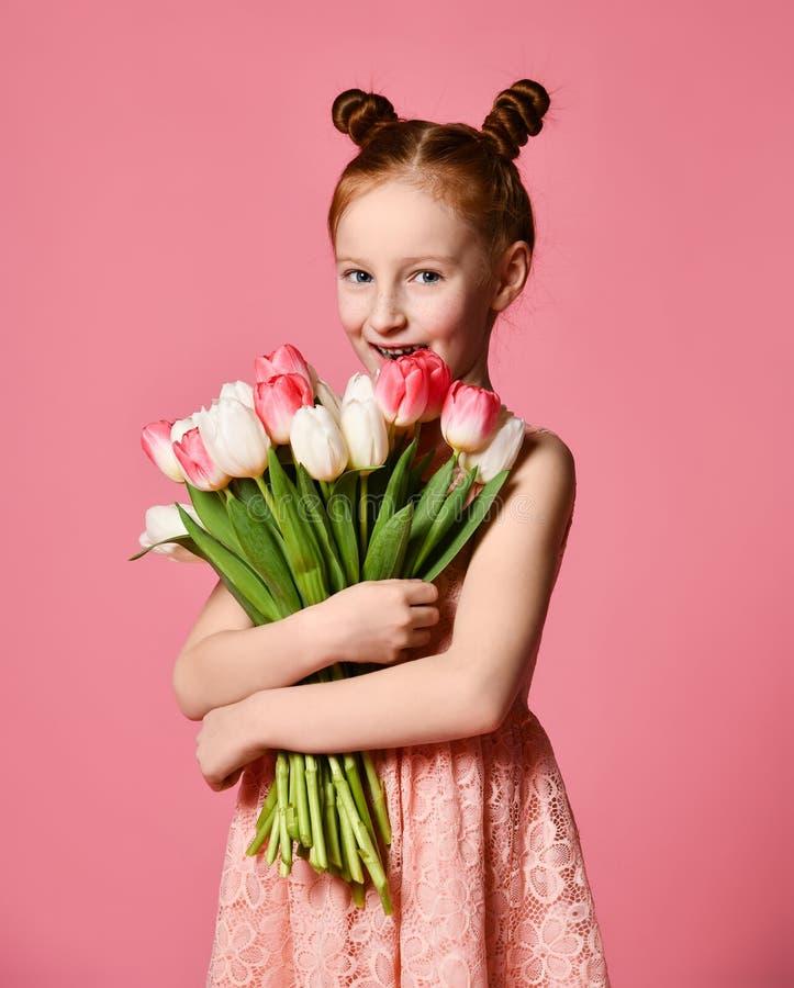 Portret van een mooi jong meisje die in kleding groot die boeket van irissen en tulpen houden over roze achtergrond worden geïsol stock afbeeldingen