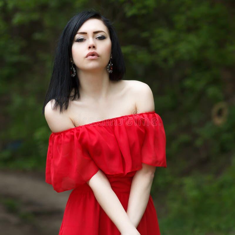 Portret van een mooi jong meisje met groene ogen en naakte schouders, in een rode kleding op een groene achtergrond de zomeraard royalty-vrije stock fotografie