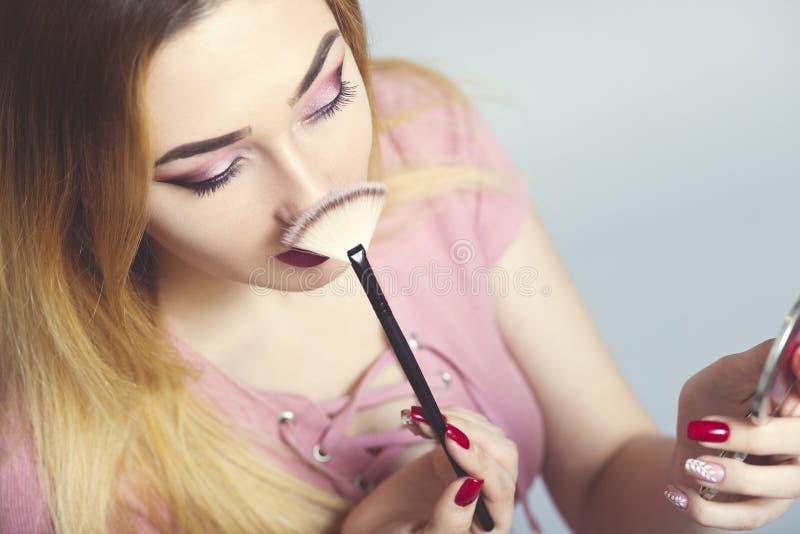 Portret van een mooi jong meisje met make-upborstel in een studio, een vrouwengezicht, schoonheidsmiddelen en natuurlijk schoonhe royalty-vrije stock foto's