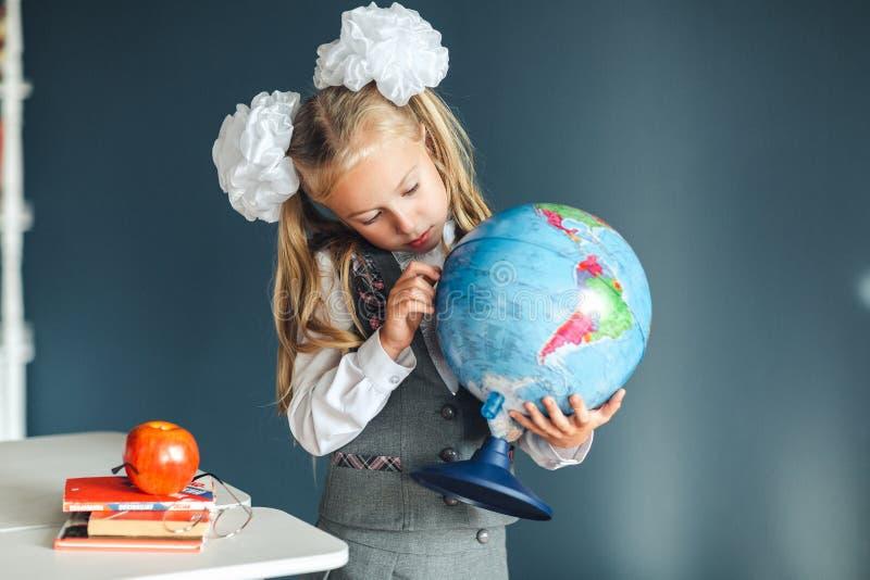 Portret van een mooi jong schoolmeisjemeisje in school eenvormig met witte bogen die de bol onderzoeken door meer magnifier Dag v stock foto