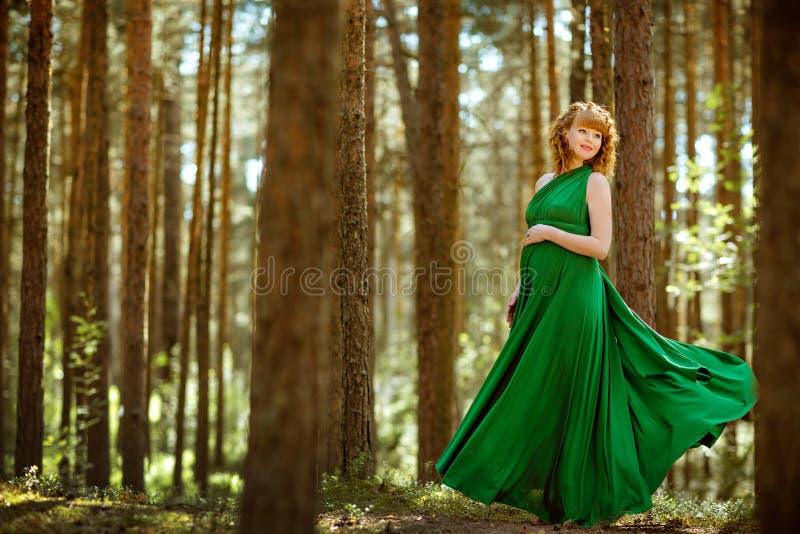 Portret van een mooi krullend haired zwanger meisje in groen FL royalty-vrije stock afbeeldingen