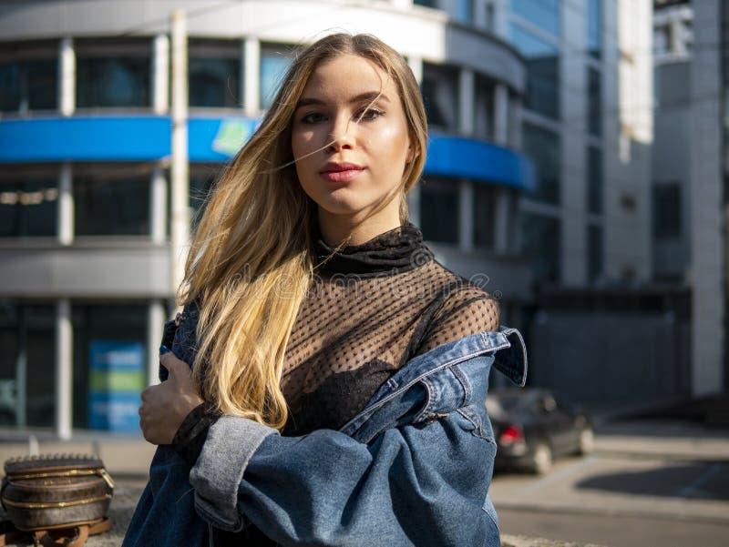Portret van een mooi meisje in een denimjasje op de achtergrond van een modern commercieel centrum op een heldere zonnige dag stock foto's