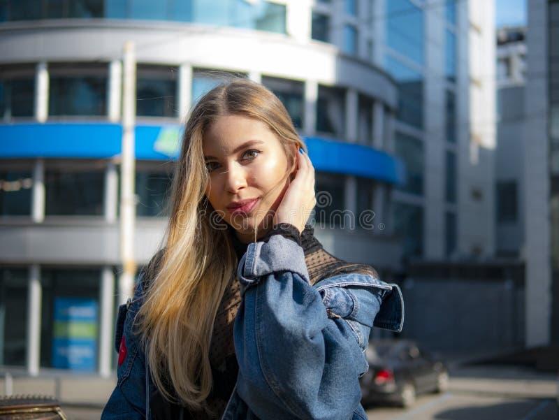 Portret van een mooi meisje in een denimjasje op de achtergrond van een modern commercieel centrum op een heldere zonnige dag royalty-vrije stock afbeeldingen