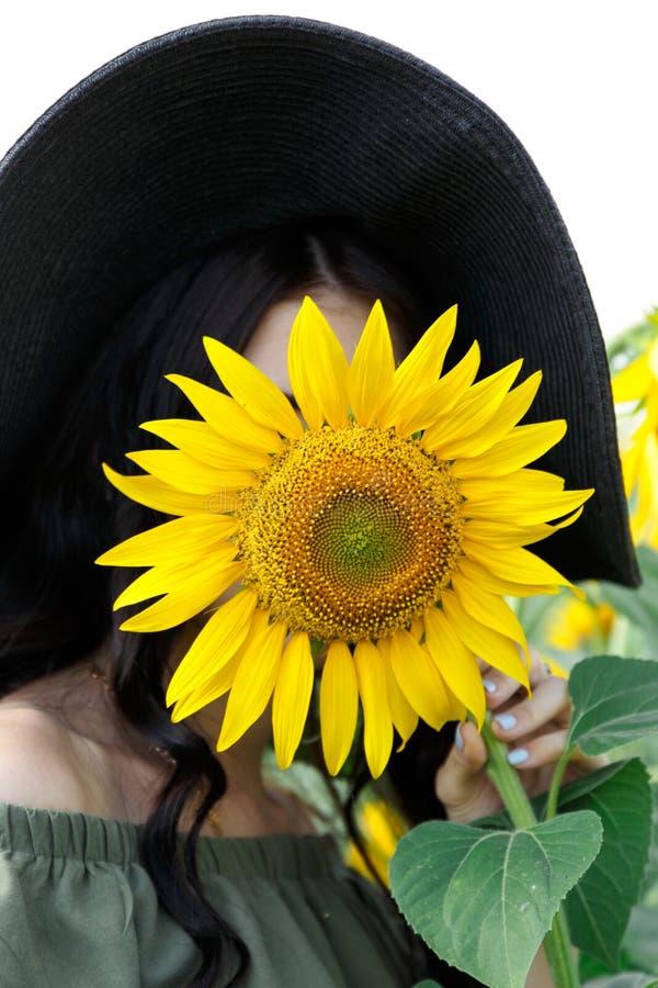 Portret van een mooi meisje die haar gezicht behandelen met een zonnebloem Aard, de zomervakantie, vakantie Vrouw met lang haar i stock afbeelding