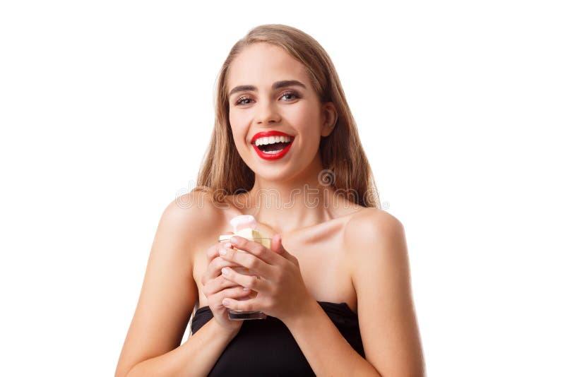 Portret van een mooi meisje die een kop van heemst houden die en camera bekijken over witte achtergrond wordt geïsoleerd stock afbeelding