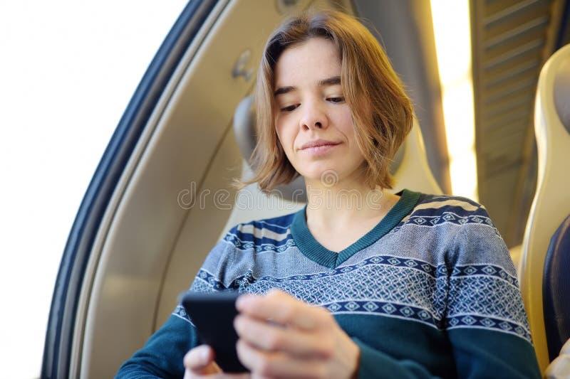 Portret van een mooi meisje die op de telefoon in een treinauto communiceren Mobiel communicatiemiddel - de vreugde van mededelin stock foto