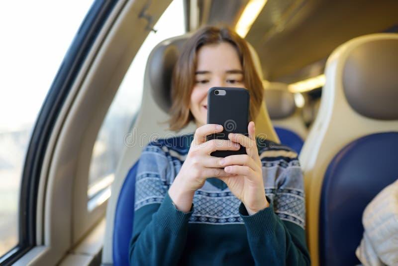 Portret van een mooi meisje die op de telefoon in een treinauto communiceren Mobiel communicatiemiddel - de vreugde van mededelin royalty-vrije stock fotografie