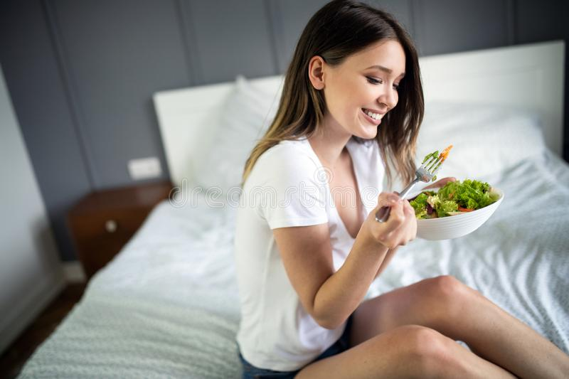 Portret van een mooi mooi meisje die verse salade van een kom eten royalty-vrije stock afbeelding