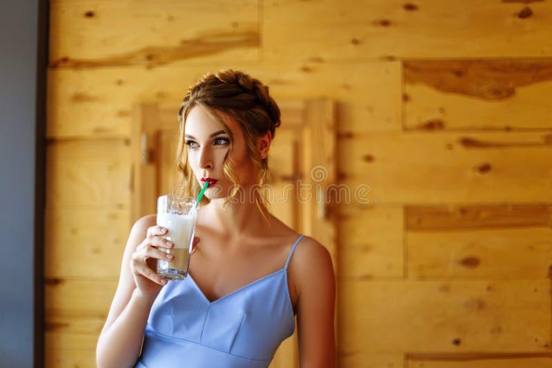 Portret van een mooi meisje in een cofee met een glas van cappuccino royalty-vrije stock foto's