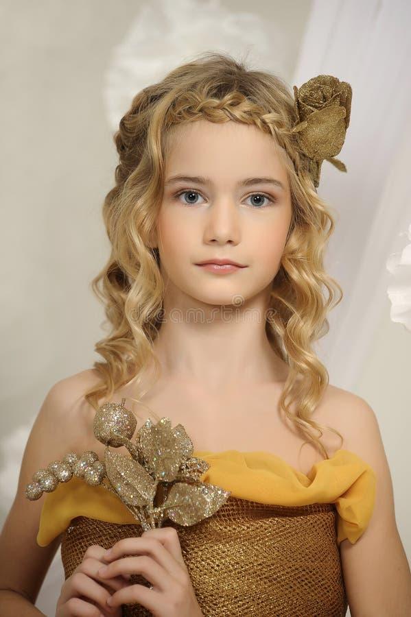 Portret van een mooi meisje in een goud royalty-vrije stock foto