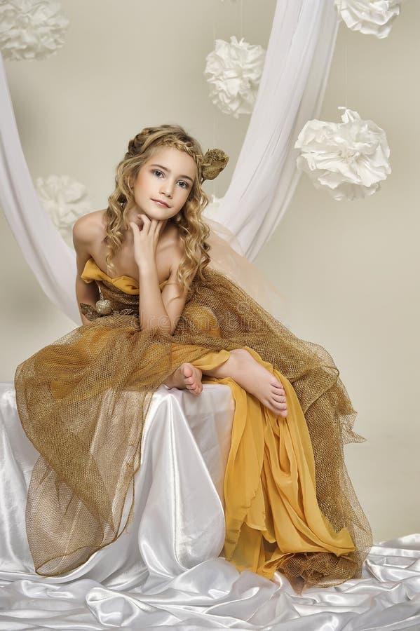 Portret van een mooi meisje in een goud stock afbeelding