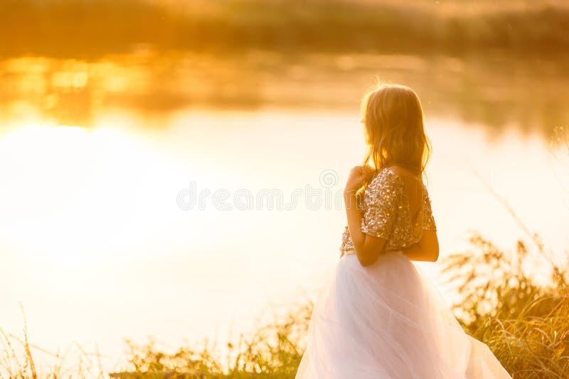 Portret van een mooi meisje in een kleding bij zonsondergang dichtbij een meer stock foto