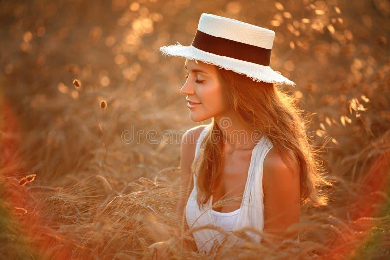 Portret van een mooi meisje in een witte kleding en hoed in fie stock foto's