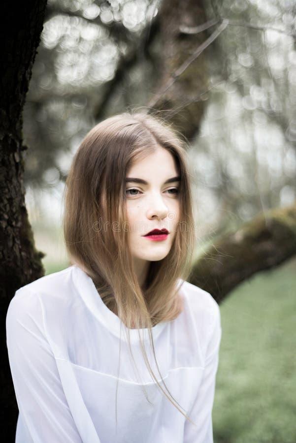 Portret van een mooi meisje in een zwarte laag op de aard royalty-vrije stock fotografie