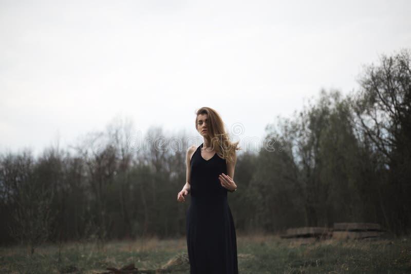 Portret van een mooi meisje in een zwarte laag op de aard stock foto