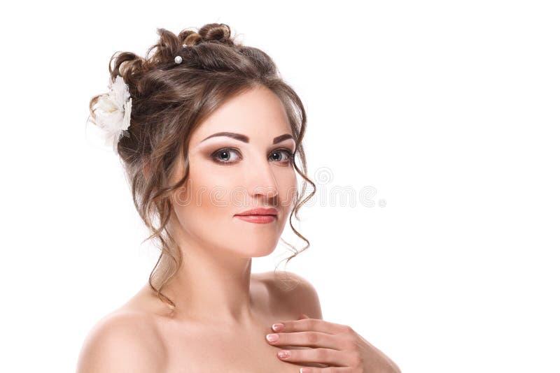 Portret van een mooi meisje in het beeld van een bruid met een witte bloem in haar die haar - op witte achtergrond wordt geïsolee stock afbeelding