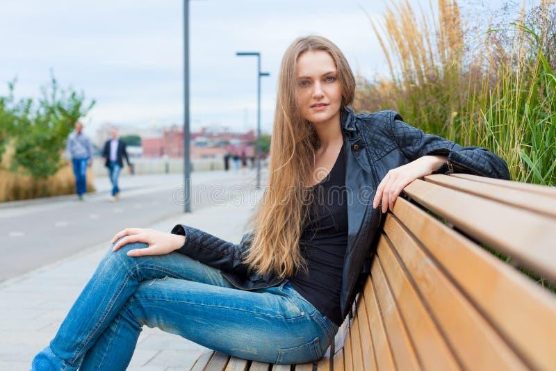 Portret van een mooi meisje in het park op de bank Sluit omhoog stock afbeelding