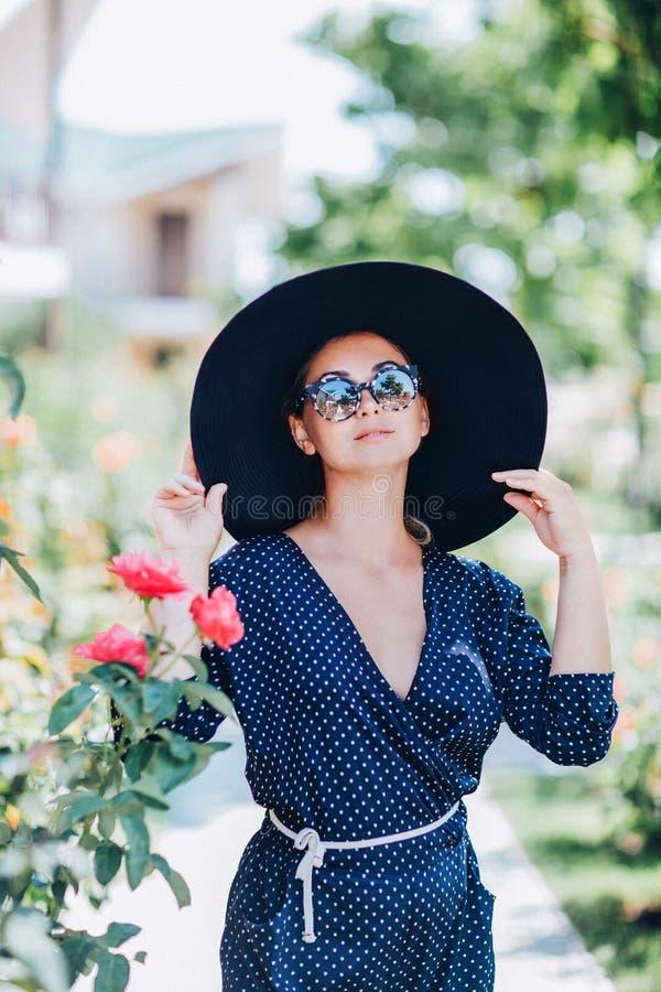 Portret van een mooi meisje in een hoed en glazen op de straat dichtbij bloeiende rozen stock fotografie