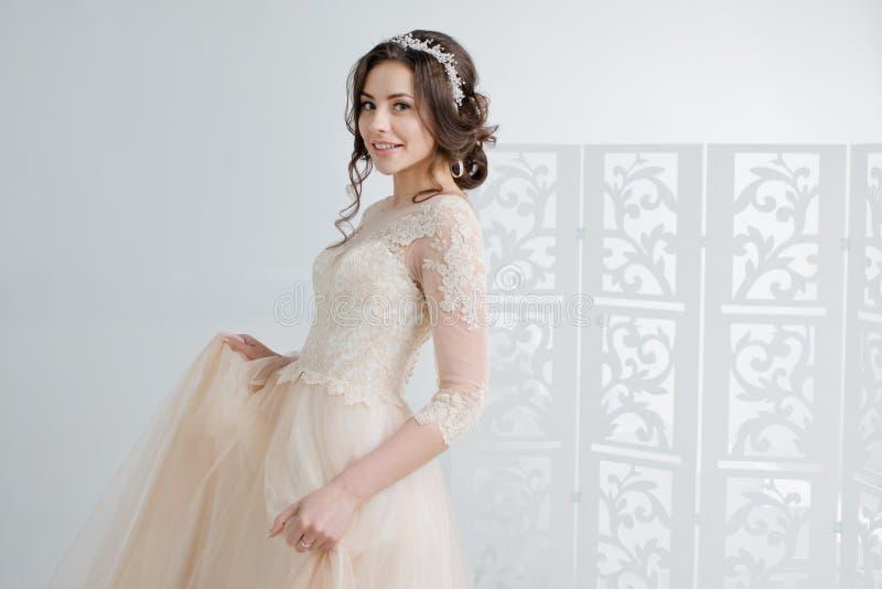 Portret van een mooi meisje in een huwelijkskleding Bruid in een luxueuze kleding, in een mooi wit binnenland stock foto's