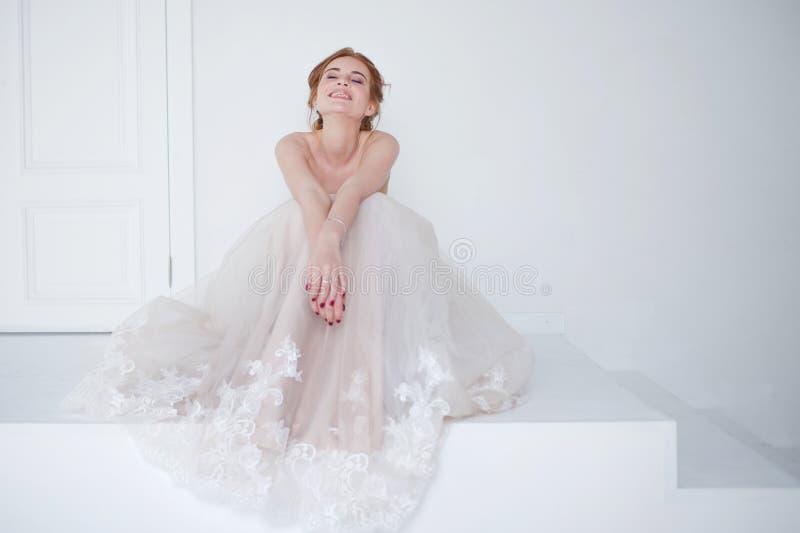 Portret van een mooi meisje in een huwelijkskleding Bruid in luxueuze kledingszitting op de vloer stock afbeeldingen