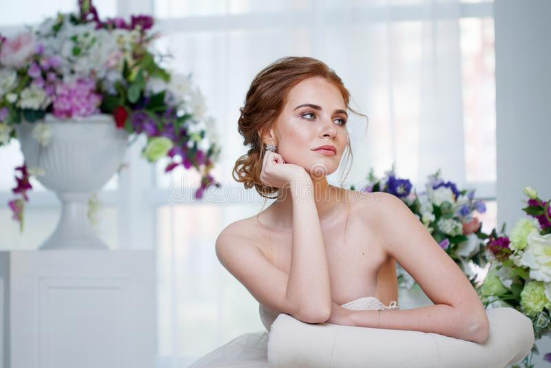 Portret van een mooi meisje in een huwelijkskleding Bruid in luxueuze kledingszitting op een stoel royalty-vrije stock foto's