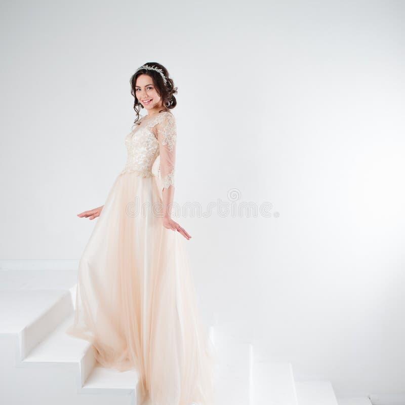 Portret van een mooi meisje in een huwelijkskleding De bruid in een luxueuze kleding die zich op de treden bevinden, beklimt omho royalty-vrije stock afbeeldingen