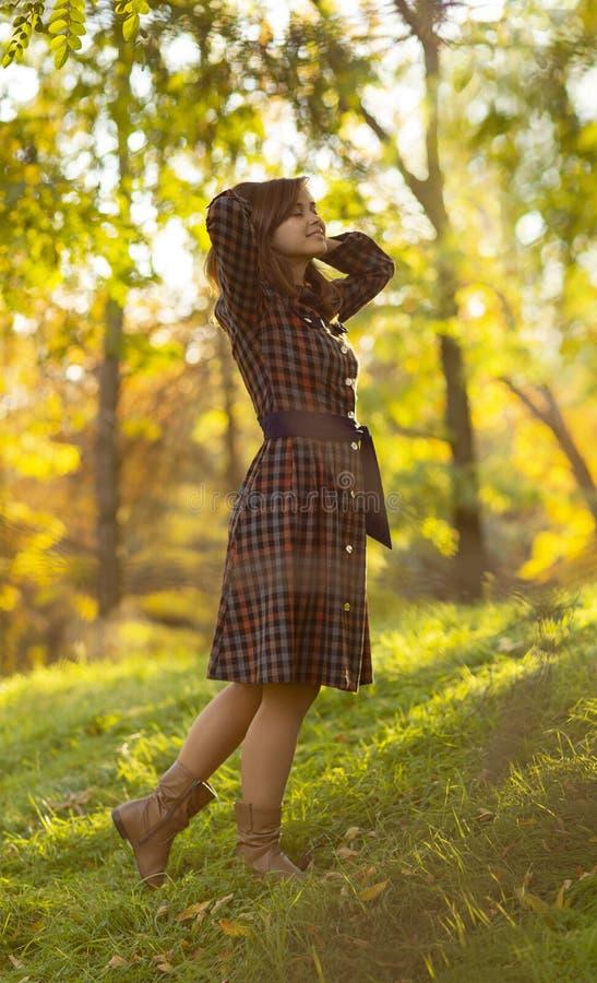 Portret van een mooi meisje in een kleding die in aard in de herfst lopen, een jonge vrouw die van de zonneschijn genieten die zi royalty-vrije stock foto