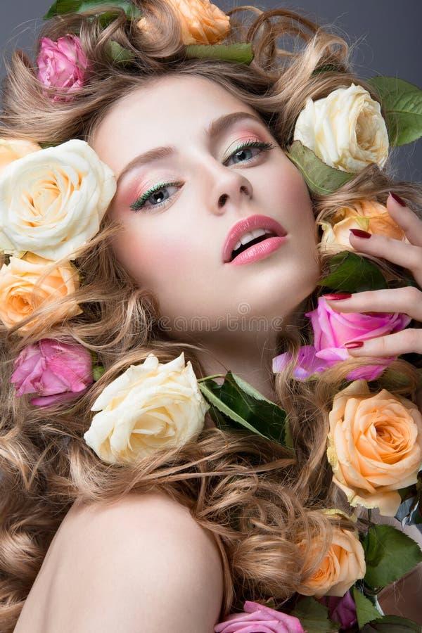 Portret van een mooi meisje met een zachte roze samenstelling en veel bloemen in haar haar Het Gezicht van de schoonheid royalty-vrije stock foto