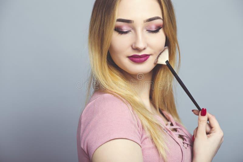 portret van een mooi meisje met make-upborstel in een studio, een vrouwengezicht, schoonheidsmiddelen en natuurlijk schoonheidsco stock foto's
