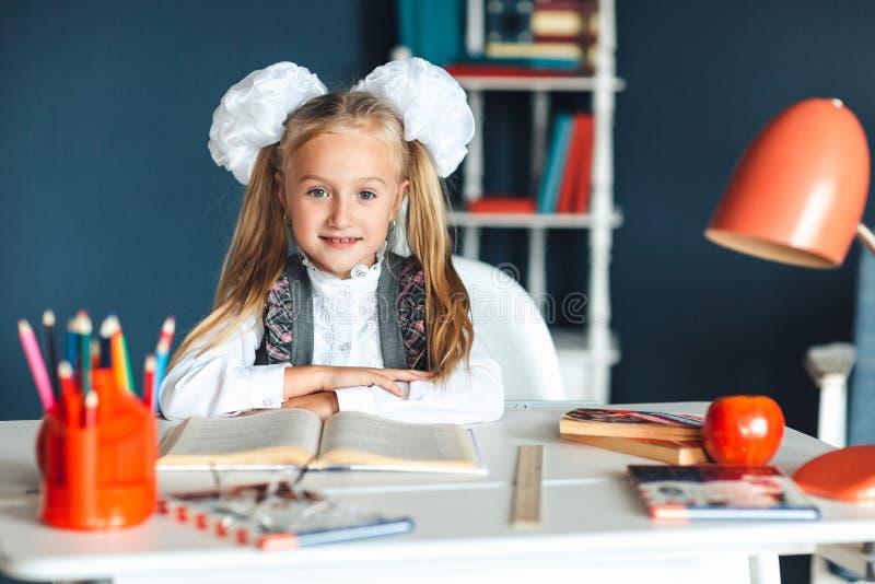 Portret van een mooi meisje thuis Weinig schoolmeisje met wit buigt zitting bij de lijst en het bestuderen Onderwijs en school royalty-vrije stock fotografie