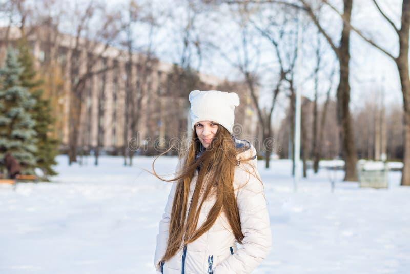 Portret van een mooi meisje in wit met zeer lang haar in de sneeuwwinter stock fotografie