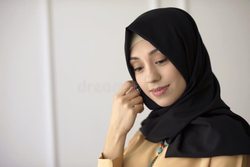 Portret van een mooi Moslimmeisje in een zwarte sjaal op zijn hoofd op een lichte klassieke achtergrond royalty-vrije stock afbeelding