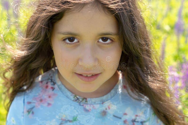 Portret van een mooi Moslimtienermeisje met bruine ogen en lang, krullend haar op een gebied van bloemen royalty-vrije stock foto