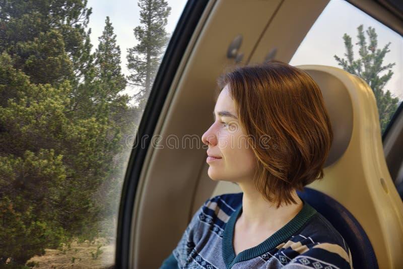 Portret van een mooi peinzend meisje die in een treinauto dromen royalty-vrije stock fotografie