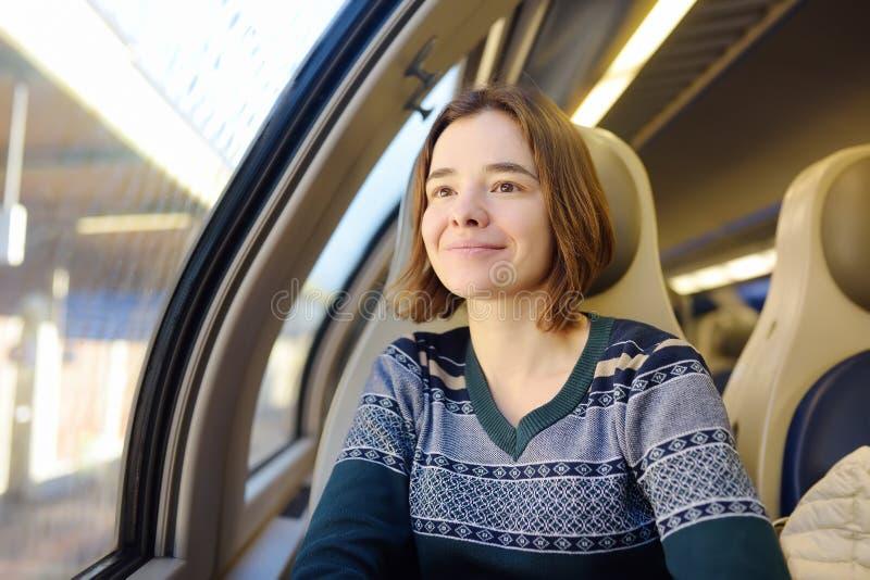 Portret van een mooi peinzend meisje die in een treinauto dromen stock afbeelding