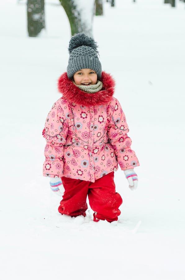Portret van een mooi peutermeisje die in openlucht met sneeuw spelen Gelukkig weinig kind die van een de winterdag in het park ge royalty-vrije stock foto's