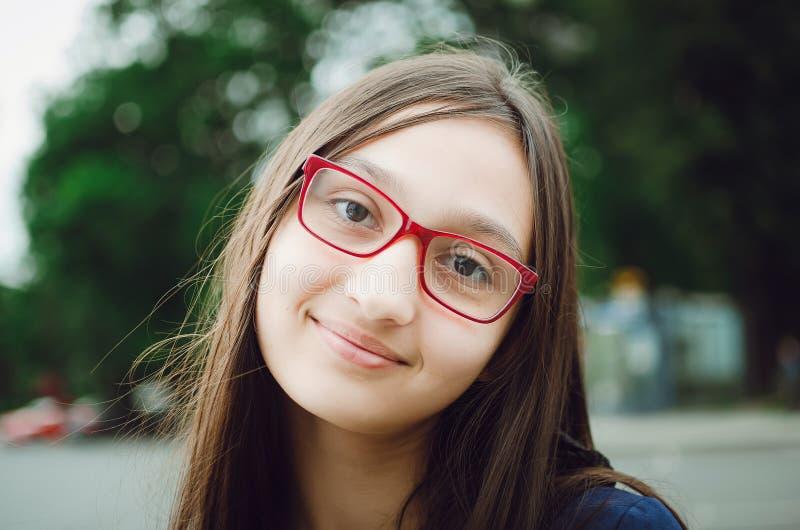 Portret van een mooi tienermeisje met glazen Het natuurlijke stellen op de straat royalty-vrije stock afbeeldingen