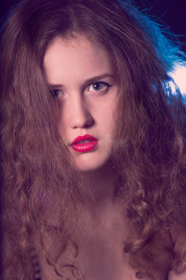 Portret van een mooi tienermeisje met lange krullende haren stock fotografie