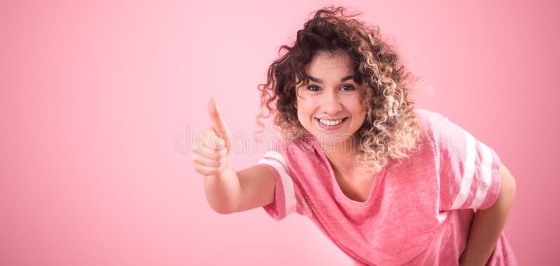 Portret van een mooi vrolijk meisje met krullend haar op een roze achtergrond stock afbeeldingen
