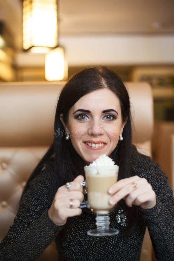 Portret van een mooi wijfje die latte bij een cafetaria drinken royalty-vrije stock afbeeldingen