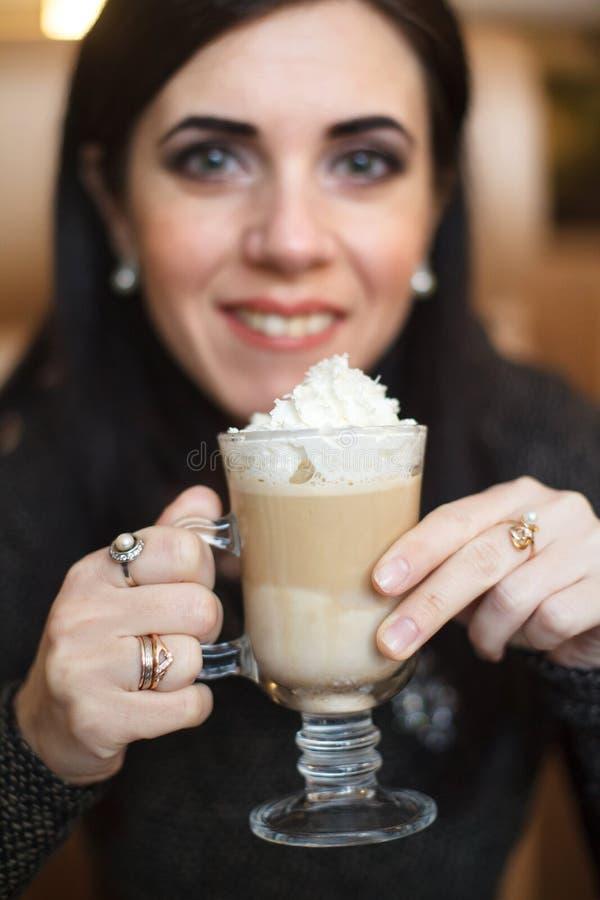 Portret van een mooi wijfje die latte bij een cafetaria drinken Selectieve nadruk royalty-vrije stock foto's