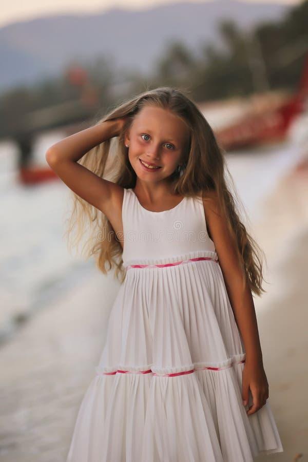 Portret van een mooi zoet meisje die met lang haar langs het strand lopen royalty-vrije stock fotografie